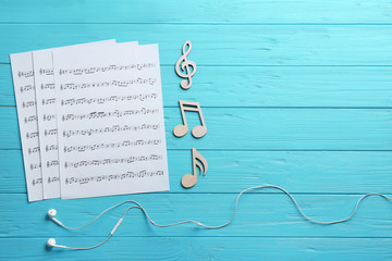 Earphones, music notes and sheets on wooden background, flat lay. Space for text