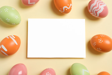 Flat lay composition of painted Easter eggs and blank card on color background, space for text