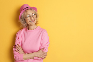 Portrait of mature woman in hipster outfit on color background. Space for text
