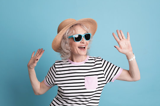 Portrait of mature woman in hipster outfit on color background