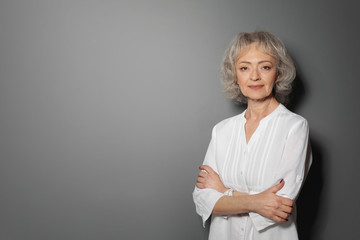 Portrait of mature woman on grey background. Space for text