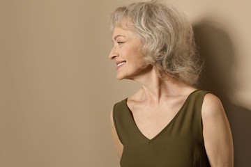 Portrait of mature woman on color background. Space for text