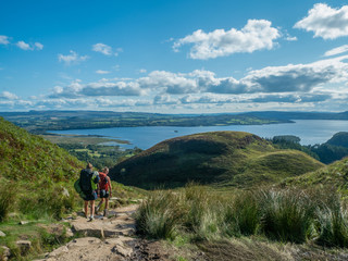 two girls hiking with beautiful lake (loch lomond) and green landscape on a sunny day