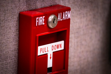"""Manual fire alarm activation pull station on wall - signage reading: """"FIRE ALARM"""" and """"PULL DOWN""""."""