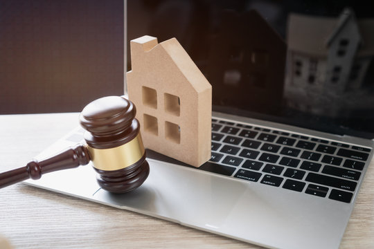 Online Auction for Real Estate concept. Judge gavel and house model on Notebook computer. Ideas for housing business judgment by E-commerce online goods services digital technology held over internet