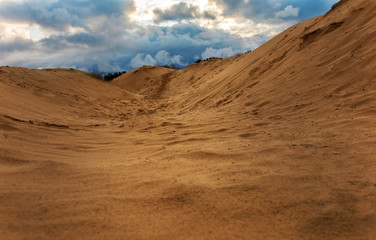 Papier Peint - volumetric clouds on a background of sandy desert at sunset