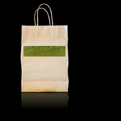 Paper shopping bag isolated on black background.