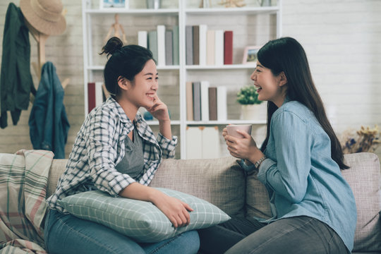 Two asian casual women relaxing on sofa with hot drink in new home. young girls chatting talking about funny things gossip laughing on couch in apartment. female roommates stay in dormitory together.
