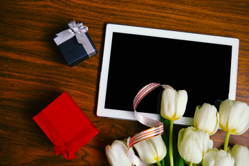 Flat lay photo with white tulips and tablet computer with black screen. 8 March or Easter greeting card. Valentines Day. Mothers Day