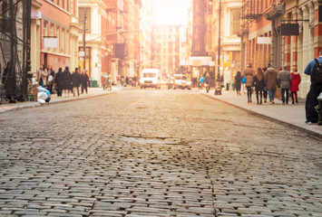 View of cobblestone covered Greene Street with bright sunlight background in the SoHo neighborhood of Manhattan, New York City