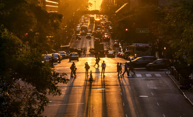 People standing in the intersection of 42nd Street and Second Avenue watching the sunset between the buildings of Midtown Manhattan in New York City