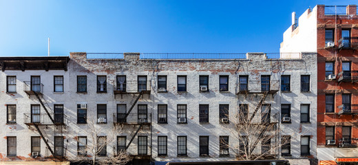 Exterior view of the facade of an old brick apartment buildings with windows and fire escapes in New York City
