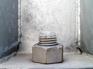 close up gray metal bolt screw and nut for hold the base structure of steel pole, old big nut on base of pillar with copy space, hardware for large construction