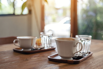 Closeup image of white mugs of hot coffee and glasses of water on wooden table in cafe