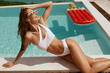 Summer fashion. Woman in swimsuit, sunglasses near swimming pool