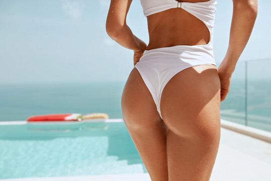 Summer body. Woman's ass in bikini swimsuit near swimming pool