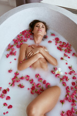 Body skin care. Woman relaxing in spa bath with milk and flowers