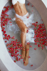 Woman's body with long legs in bath tub with flowers at day spa