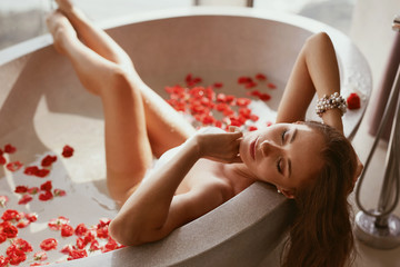 Spa therapy. Woman relaxing in bath tub with flowers at day spa