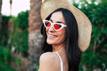 Travel bug. Gorgeous girl with long dark hair, brilliant smile and hazel eyes wearing camel hat and cat shaped sunglasses in front of deep green bushes and a palm tree.