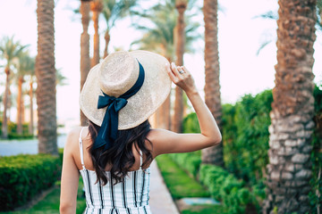 Travel enthusiast. A photo from aback of a woman with long curly hair in beige hat with silk bow on it and stripped jumpsuit among light green bushes and high palm trees.