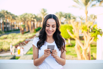 Cool it. Beautiful eye catching girl in focus of the camera, among the marvelous view of the majestic palm trees , green bushes and masonry path, is holding her phone with her tender hands.