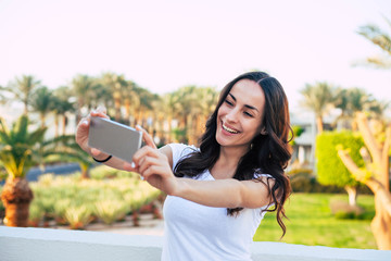 Commemorative photo. Heartening girl with perfect smile and long hair is taking a selfie in front of colorful background of vibrant green trees, light green bushes ,grass and clear blue sky.