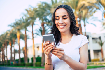 Touch of delight. Bodacious girl with long dark hair white smile and perfect body shape is holding her white phone among palm trees full of sun lights and green grass.