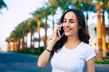 Gentle call. Pleasant woman with dark brown hair, glowing skin and stunning smile is,making a call with the help of her white phone in front of  concrete pavers road and green palm trees line.