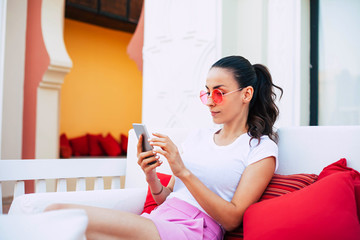 A little paradise. Relaxed woman with ponytail in white t-shirt and pink shorts accompanied with red sunglasses framed with gold color sitting on the lounge with red pillows.