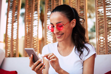 Exiting message. Cute young girl in white t-shirt and round red sunglasses in front of wooden decorations and white sofa is using her phone in the lobby of the hotel.