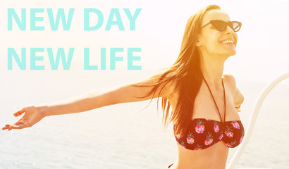New day New life! Hilarious girl with a stunning smile and long hazel hair in swimwear full of bright pink and green pineapples and cat-chapped black sunglasses in front of blue sea water.