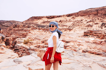 On my way to the miracle. Active pleased woman with the white backpack, kerchief with chess print over her head and vermilion red jacket over her waist is on her way to the sandy rocks.