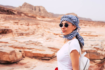 Interested in beautiful surroundings young girl in bright white t-shirt, three-color kerchief over her long brown hair and dark oval sunglasses is standing among the high sandy rocks