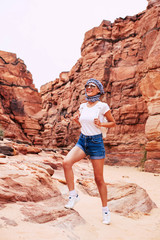 A rock step. Cheered and tanned girl near the brownish rocks wearing denim shorts, white t-shirt, creamy sneakers, sunglasses with a mirror effect and a kerchief of white,dark blue and black colors.