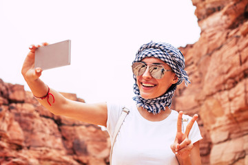 Peace to the world. Superb woman in comfortable outfit , with tanned and glowing skin, thin and elegant hands is making a selfie of herself and sending peace to the world.