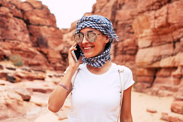 A picture of  brownish rocks on the background and a joyful girl first to the camera who is talking to someone by her smartphone and wearing light colored outfit with sunglasses.