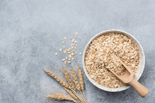Rolled oats, oat flakes in bowl on concrete background. Top view with copy space. Healthy food, healthy eating, dieting, weight loss and health care concept