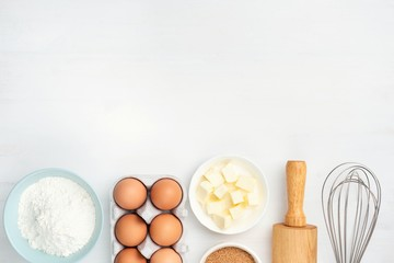 Baking ingredients and kitchen utensils on white background. Chicken eggs, butter, sugar, flour, rolling pin and whisker. Cooking, baking, pastry or cookie dough ingredients Papier Peint