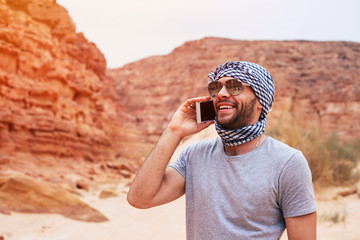 Hello from the nature. Hilarious man in grey t-shirt and kerchief, with brilliant smile all over his face which were caused by the pleasant conversation.