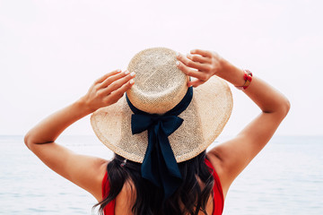 Blushing violet. Tanned girl in rose-red swimwear and beige hat with a black silk bow on it is raising her hands up to fix the hat and catch the sew breathe.