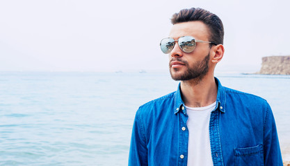 Ally of the sky. Pretty boy in denim shirt and sunglasses , with dark hair and beard is watching through the beauty of the point where sky is connecting with the sea.