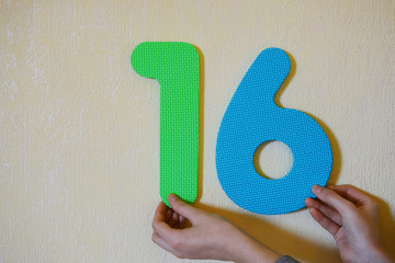 Hands holding number sixteen on yellow wall background with copy space for text. 16th anniversary birthday design or educational children toys for learning colors and numbers concept.