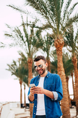 Small talk. Photo of turquoise sky, grand green palm trees, terrace of the hotel and a smiling man in denim shirt using his smartphone.