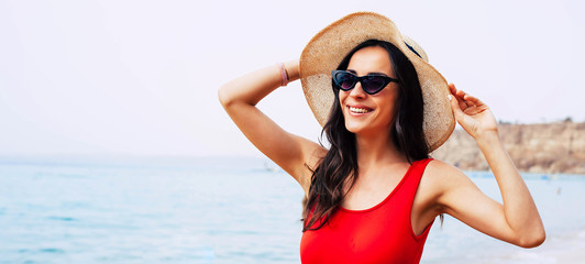 All charm and sunshine. Chic girl in front of light blue sea water is wearing bright swimsuit, taupe round hat and cat-shaped black sunglasses and welcoming the morning sun.