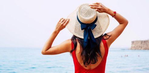 Aback photo of a woman in red swimwear,matching bracelet and camel hat with silk bow on it who is taking sunbathes in the sea shore.