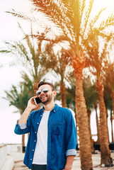 Fascinating man is paying attention to the pleasant talk in front of powder-blue sky full of golden lights of the sun set and stunning green palms.