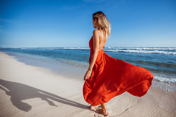 The girl is on the white sand on the beach in a red flying dress. Photo without Face, back to us.