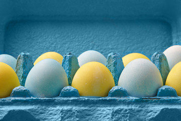 Close-up multicolored painted in yellow blue eggs in a blue cardboard box around blue background with copy space. Easter composition.