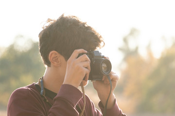 young boy with a retro camera doing photography on a summer day
